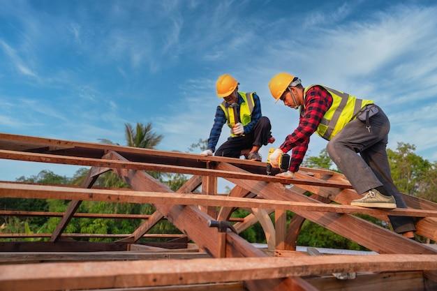 Aziatische bouwvakker installeert nieuw dak, dakgereedschap, elektrische boor gebruikt op nieuwe daken van houten dakstructuur, teamwerkconstructieconcept.