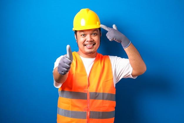 Aziatische bouwvakker met oranje veiligheidsvest en helm over blauwe achtergrond glimlachend