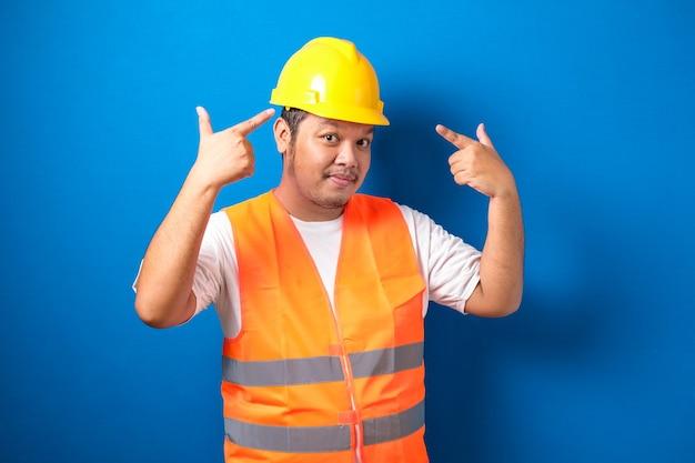 Aziatische bouwvakker met oranje veiligheidsvest en helm