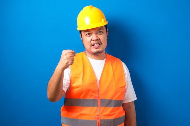 Aziatische bouwvakker met oranje vest en veiligheidshelm met gebalde vuist