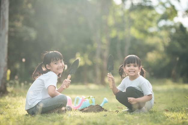 Aziatische broer of zus plant samen een jonge boom op zwarte grond als een veilige wereld in de tuin op een zomerdag. boom planten. kindertijd en outdoor vrijetijdsconcept.