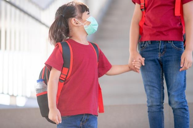 Aziatische broers en zussen van de basisschool gaan hand in hand. zus en meisje met rugzak achter de rug. begin van de lessen. eerste dag van de herfst.