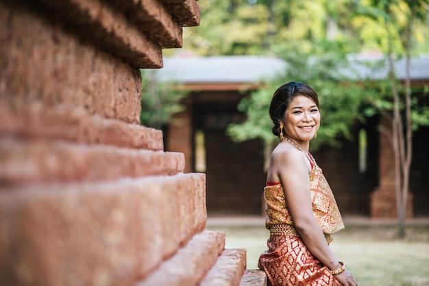 Aziatische bruid die in oude tempel post
