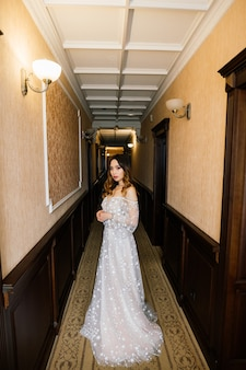 Aziatische bruid in trouwjurk in hotel zittend op het bed, staande in de buurt van venster, ochtend