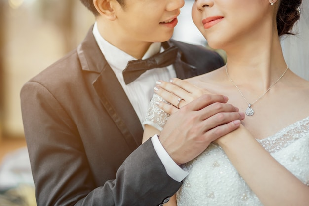 Aziatische bruidegom en aziatische bruid zijn dicht bij elkaar en staan op het punt elkaar te kussen met een lachend en blij gezicht. ze houden handen samen.
