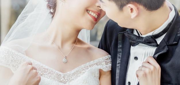 Aziatische bruidegom en aziatische bruid zijn dicht bij elkaar en staan op het punt elkaar te kussen met een lachend en blij gezicht.