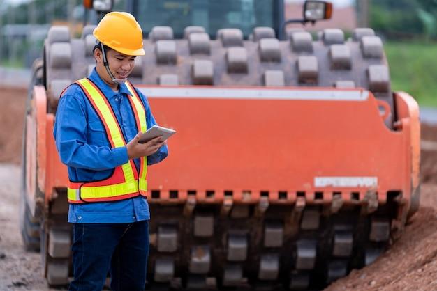 Aziatische burgerlijk ingenieur draagt een helm op de wegenbouwplaats.
