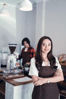 Aziatische caféeigenaar die aan camera glimlacht