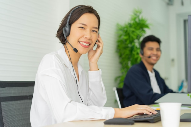 Aziatische call center vrouw agent glimlachend werken in operatiekamer aan desktop tafel