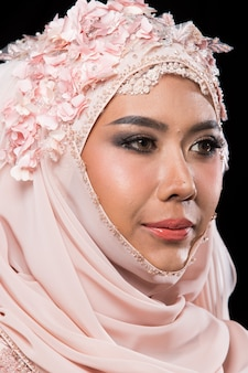 Aziatische charmante moslim arabische bruid in lace bead embroidery sweet pink oude roos trouwjurk en hijab hoofddoek, close-up op fashion make-up eyes face, studio verlichting zwarte achtergrond geïsoleerd.