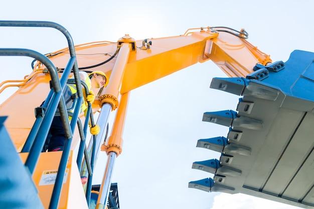 Aziatische chauffeur staande op bouwmachines op de bouwplaats