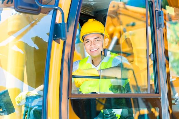 Aziatische chauffeur zit in de cockpit van bouwmachines van de bouwplaats