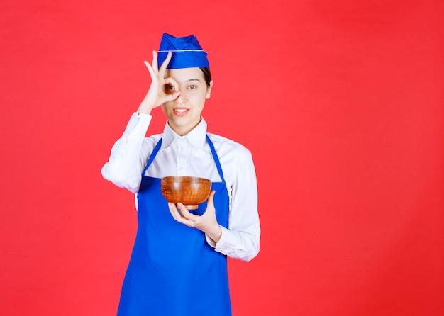 Aziatische chef-kok die in blauwe schort een aardewerkkom groene thee of noedels houdt en over haar vingers kijkt.