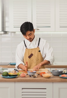 Aziatische chef-kok rollende sushi met promo van bamboemat voor online bezorgservice voor eten