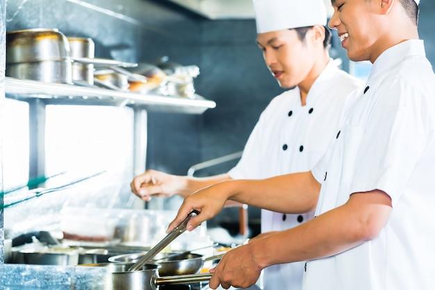 Aziatische chef-koks die in restaurant koken