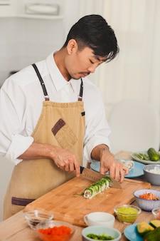 Aziatische chef-kokuniform snijden verse sushi-broodjes eten bezorgen online service japanse keukenbroodjes