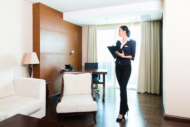 Aziatische chinese huishoudmanager of assistent die de kamer of het pak van een hotel bestuurt of controleert met een checklist op netheid