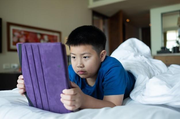 Aziatische chinese jongen die smartphone speelt, kind gebruikt telefoon en speelt spel, verslaafd spel en tekenfilm Premium Foto