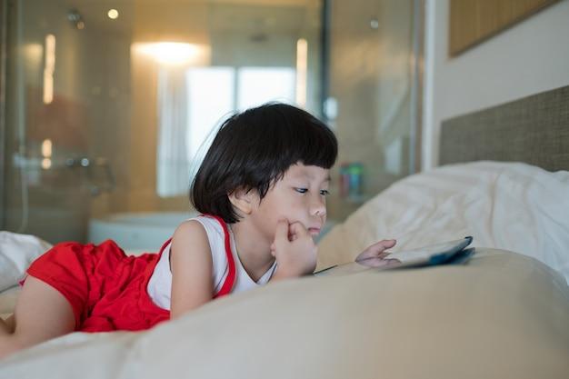 Aziatische chinese jongen spelen op smartphone in bed