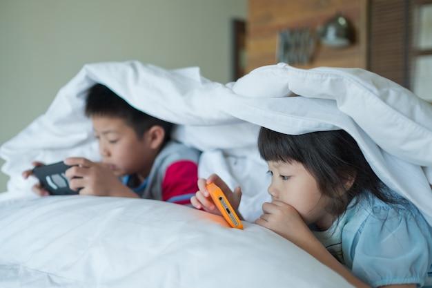 Aziatische chinese kinderen spelen op smartphone in bed