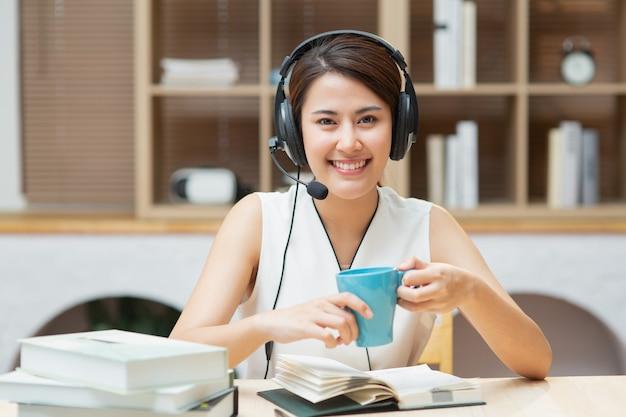 Aziatische chinese vrouw die met hoofdtelefoons camera bekijkt die online cursus of sollicitatiegesprek leert