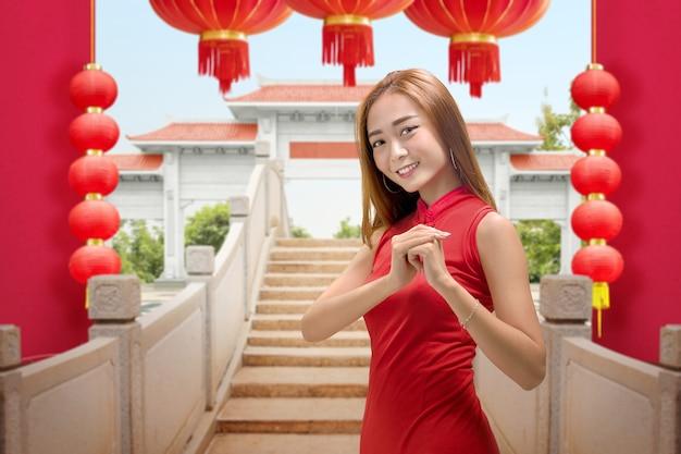 Aziatische chinese vrouw in een cheongsamjurk met gefeliciteerd gebaar. gelukkig chinees nieuwjaar