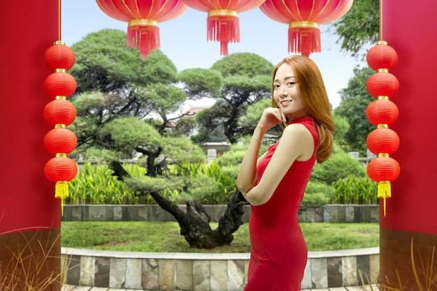Aziatische chinese vrouw in een cheongsamjurk viert chinees nieuwjaar. gelukkig chinees nieuwjaar