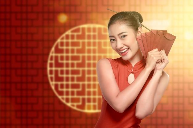 Aziatische chinese vrouw in een cheongsamkleding die rode enveloppen houdt