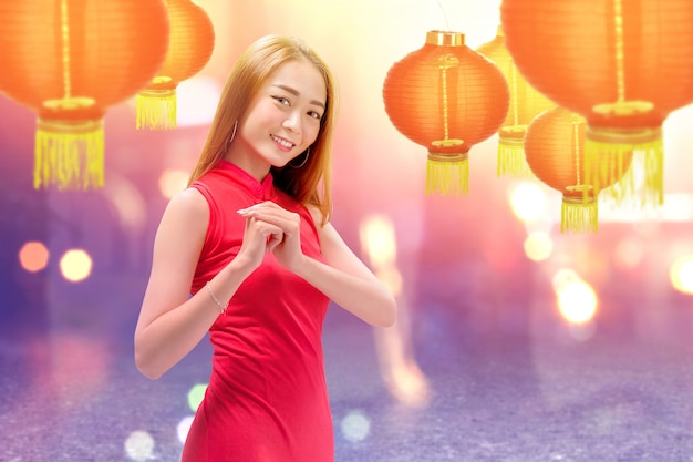 Aziatische chinese vrouw in een cheongsamkleding met gefeliciteerdgebaar