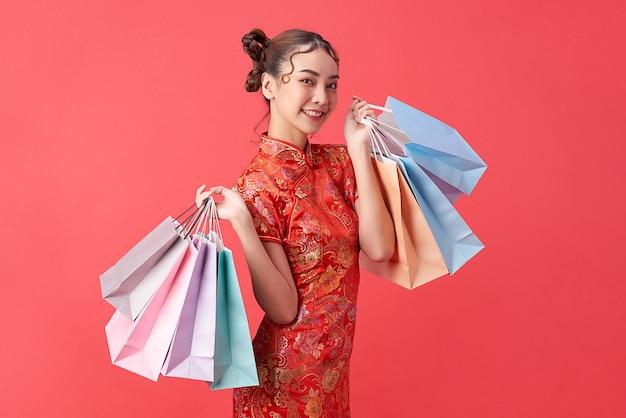 Aziatische chinese vrouw in traditionele kleding op rode achtergrond met boodschappentassen. chinees nieuwjaarsfeest.