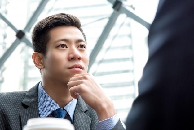 Aziatische chinese zakenman die aan zijn partner met oogcontact luistert