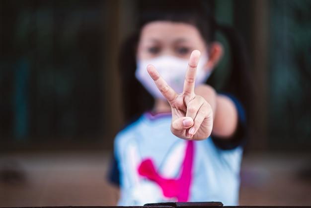 Aziatische close-up van klein kindmeisje heft twee v-vormvingers op draagt een masker om coronavirus in veiligheid te brengen ter ondersteuning van de strijd tegen de epidemie van de ziekte covid 19 thuis
