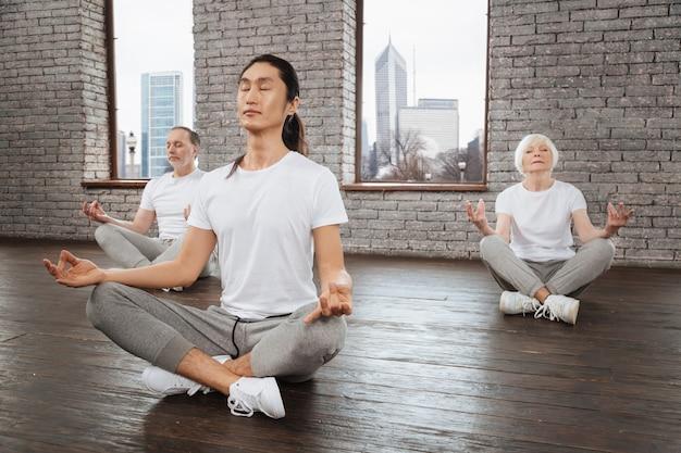 Aziatische coach die zijn ogen dicht houdt terwijl hij zijn handen op de knieën legt terwijl hij ontspannen is