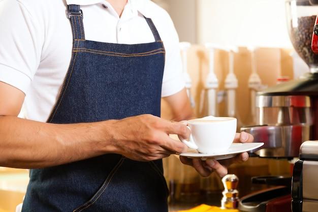 Aziatische coffeeshop - barista presenteert koffie