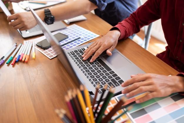 Aziatische collega's ontwerper tekening schetsen op grafische laptop.