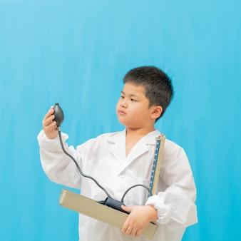 Aziatische cutea jongen houdt manometer op blauwe achtergrond,