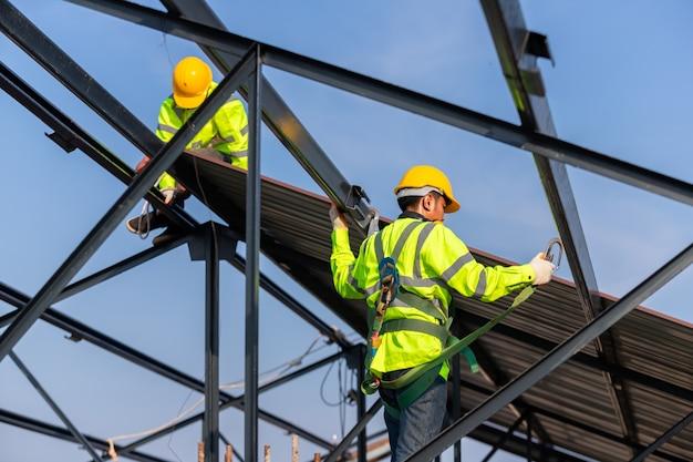 Aziatische dakbouwvakker draagt veiligheidshoogte-uitrusting om het dakframe te installeren, valstopapparaat voor werknemer met haken voor veiligheidsharnas op de bouwplaats.