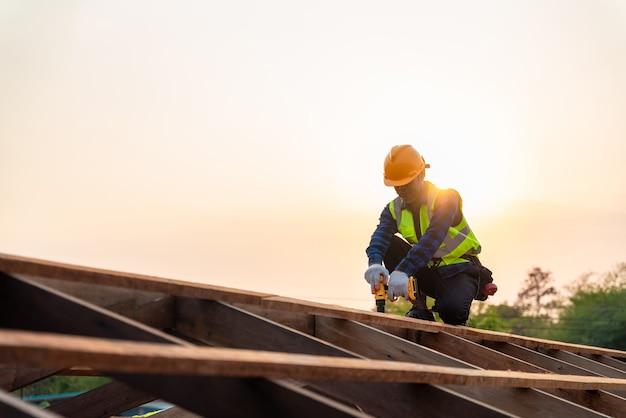 Aziatische dakdekker die werkt aan de dakstructuur van het bouwen op de bouwplaats, dakdekker met behulp van lucht of pneumatisch schiethamer en installeren op houten dakstructuur.