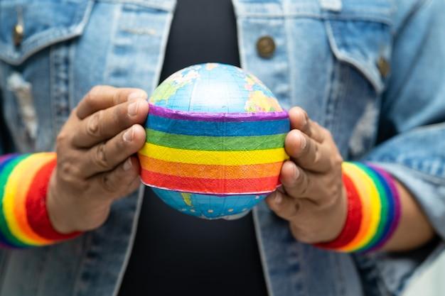 Aziatische dame die een blauwe spijkerjas of een denimoverhemd draagt en een regenboogvlag houdt met een wereldbolsymbool van de lgbt-trotsmaand