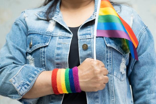 Aziatische dame die het blauwe jasje of het denimoverhemd van jean draagt en de vlag van de regenboogkleur houdt
