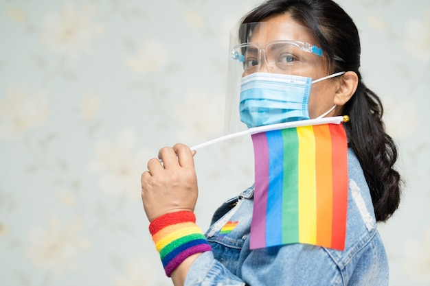 Aziatische dame die het blauwe jasje of het denimoverhemd van jean draagt en regenboogvlag, symbool van lgbt houdt.