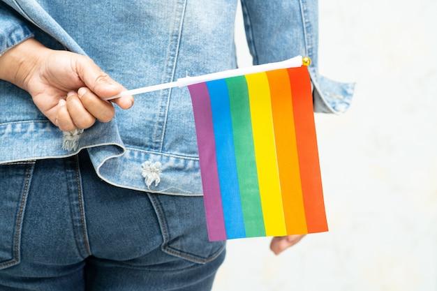 Aziatische dame die het blauwe jasje of het denimoverhemd van jean dragen en de vlag van de regenboogkleur houden, symbool van lgbt-trotsmaand.