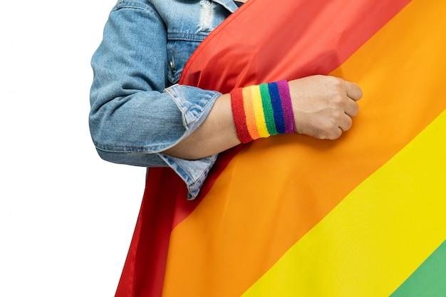 Aziatische dame die het blauwe jasje van jean dragen die de vlag van de regenboogkleur, symbool van lgbt-trotsmaand houden.