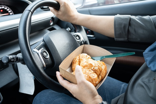 Aziatische dame die het voedsel van de broodbakkerij in auto houdt, gevaarlijk en een ongeval riskeert.