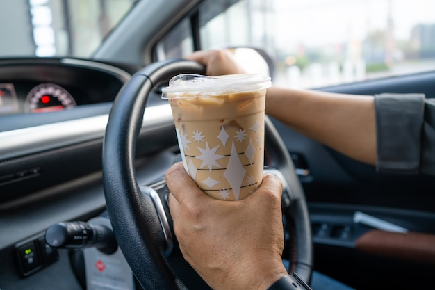 Aziatische dame die ijskoffie voor drankvoedsel in auto houdt