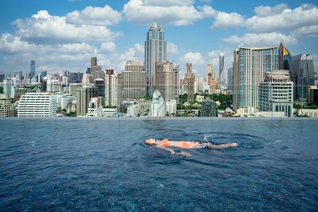 Aziatische dame geniet van zwemmen in het zwembad op het dak van het hotel in de stad bangkok, thailand