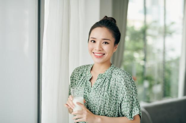Aziatische dame glas melk drinken terwijl u uit het raam met kopie ruimte kijkt