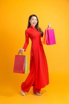 Aziatische dame in rode ao dai-jurk met boodschappentassen geïsoleerd op geel, gelukkig nieuw maanjaar
