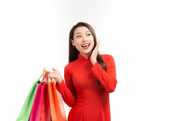 Aziatische dame in rode ao dai-jurk met boodschappentassen geïsoleerd op wit, gelukkig nieuw maanjaar