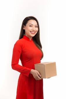 Aziatische dame in rood ao dai traditioneel kostuum met kartonnen geschenkdoos in het nieuwe maanjaar